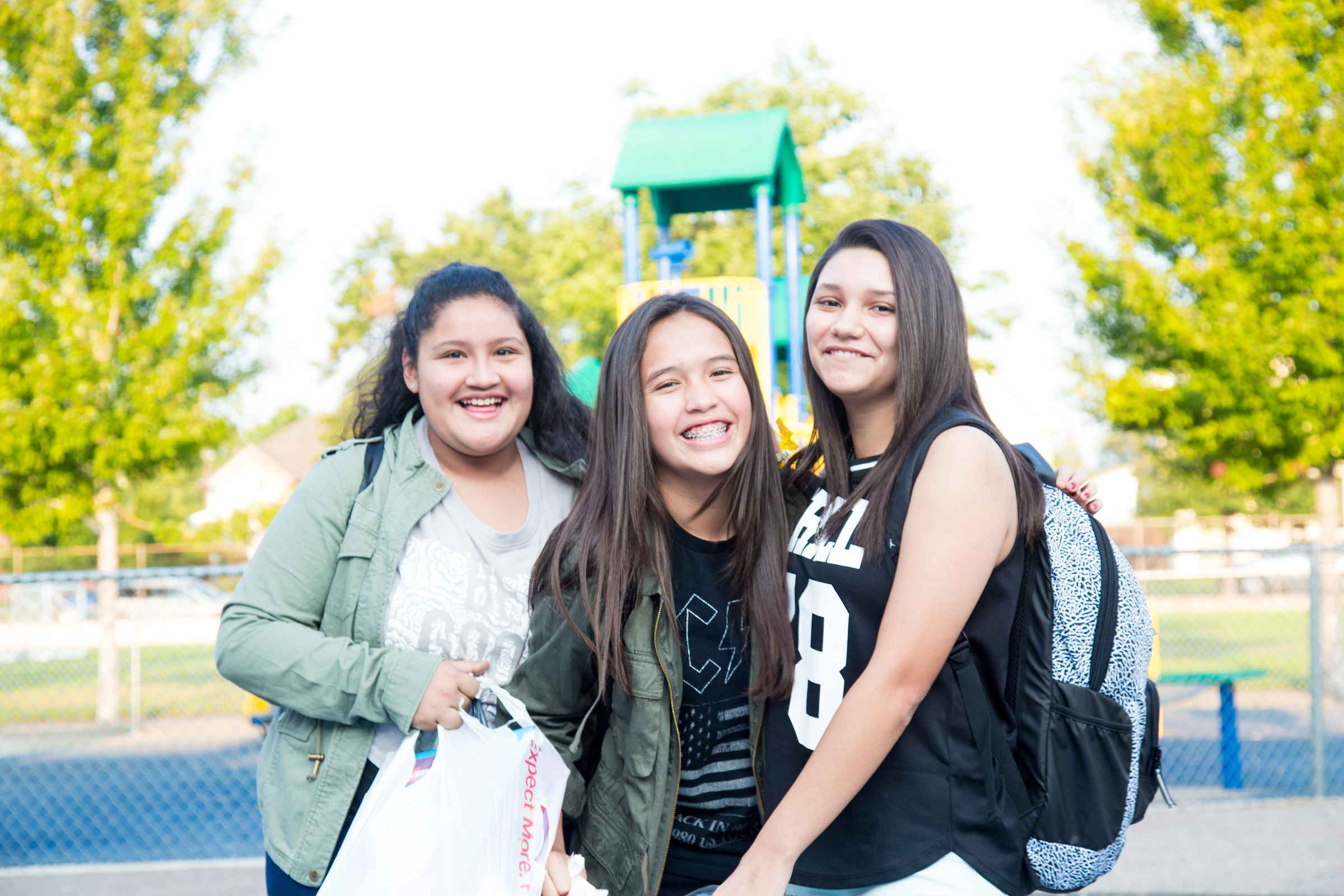 Three middle school students smile outside the playground