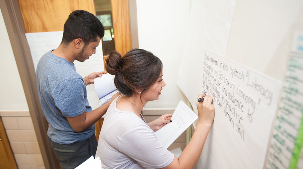 Two students write on the board during class.