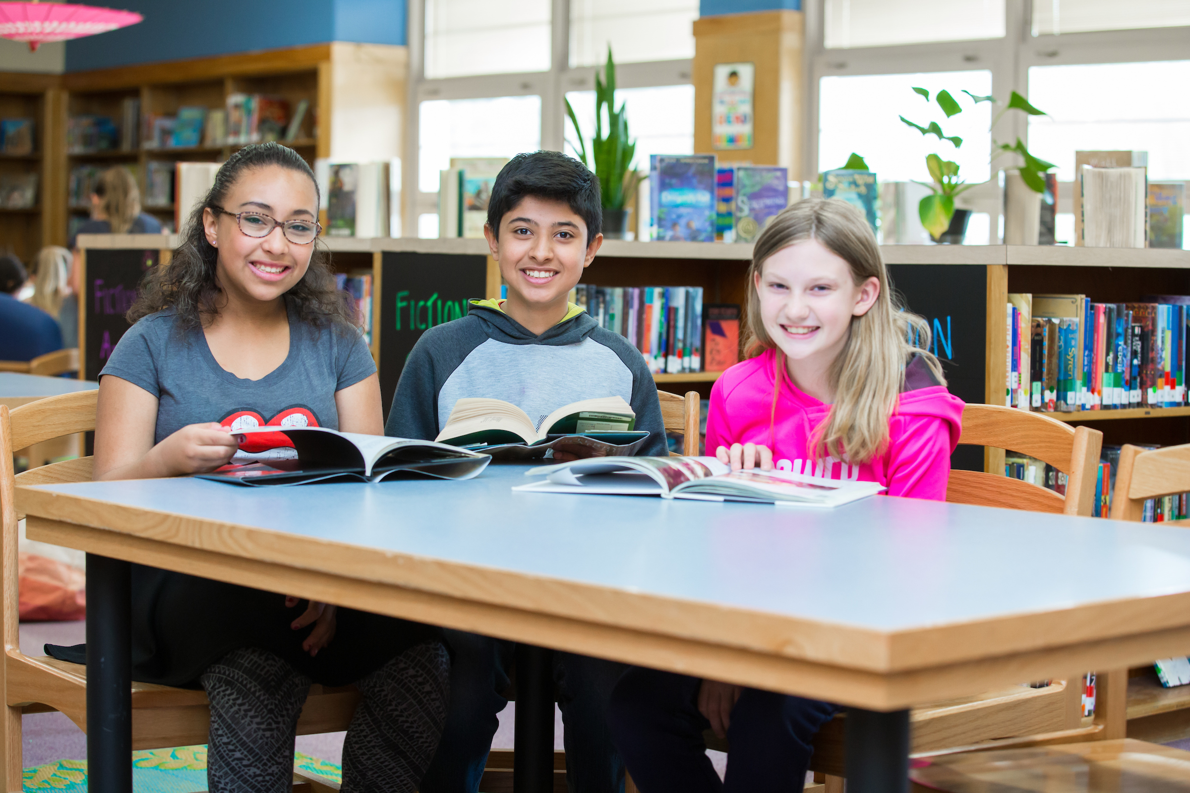 Merrill Middle School students smile with books in the library