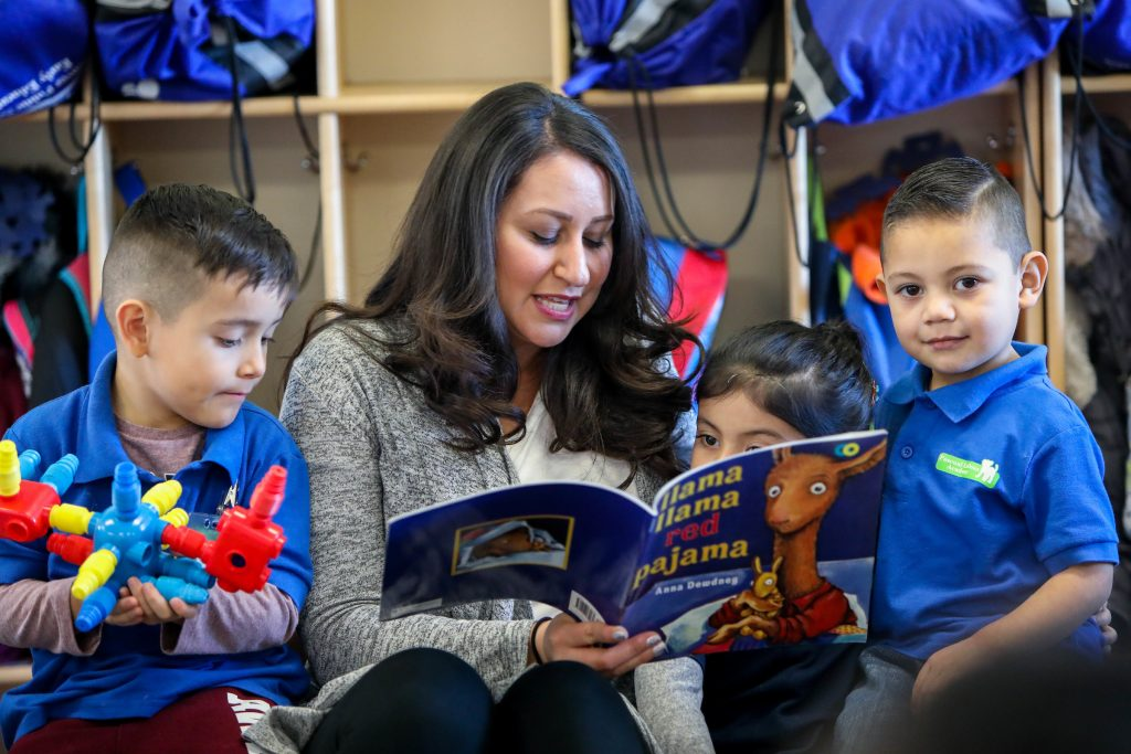 Teacher reading to two students