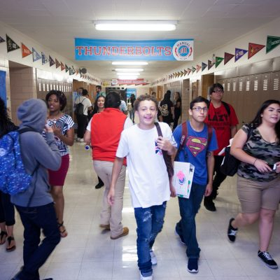 Manual High School students walk down school hallway between classes