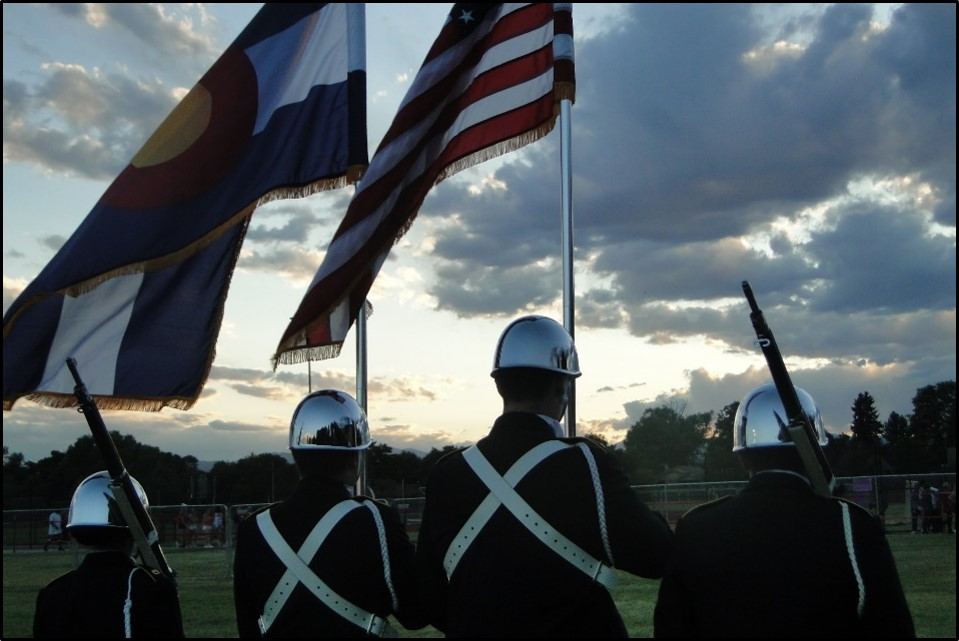 Two members of the colorguard holding the Colorado and American flags